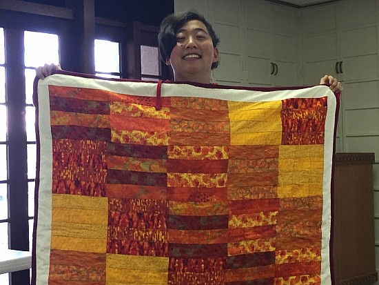 Lily and her completed quilt.